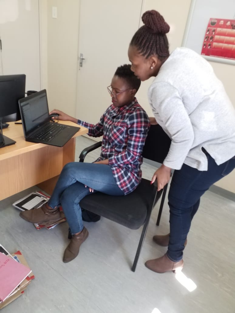 A member of staff is working an a laptop, and another is stood behind her looking at the screen