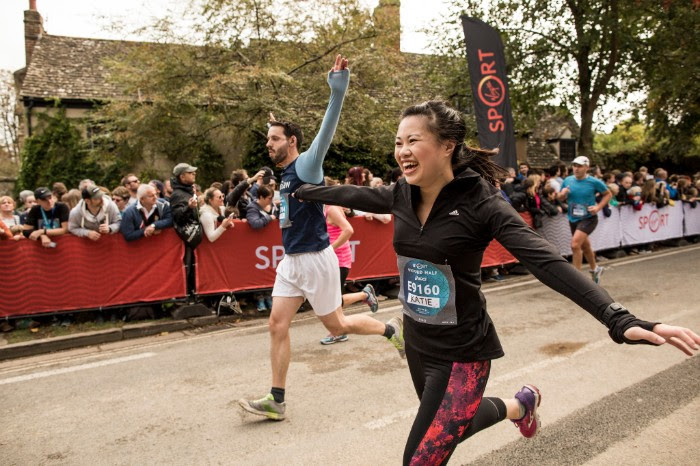 Katie Myint running with her arms out stretched at the end a race, looking very pleased