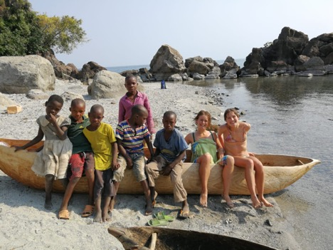 Two of the cyclists, sat on a wooden canoe on the edge of the lake with six local children