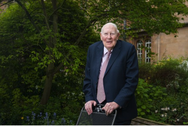 Sir Roger Bannister, stood behind a chair in a college garden