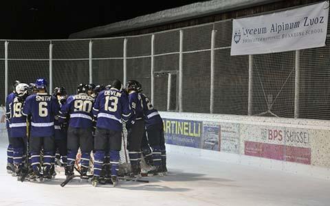 The Oxford University ice hockey team huddled together on the ice