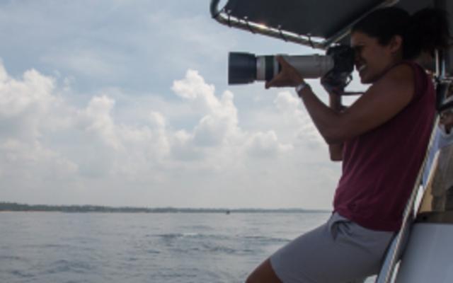Asha de Vos stood on a boat, using a camera