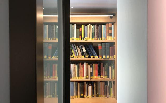A view from an open glass door of books on a shelf