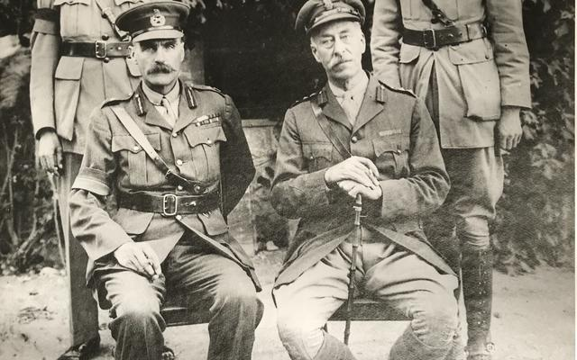 A picture of four high ranking military officials, with two seated and two standing behind them