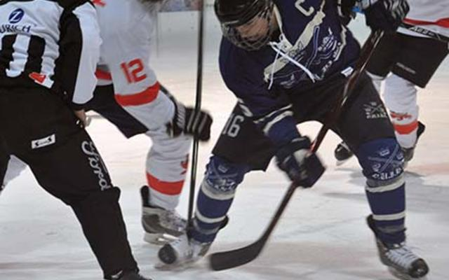 Two ice hockey players - one in white, one in blue - have a face-off