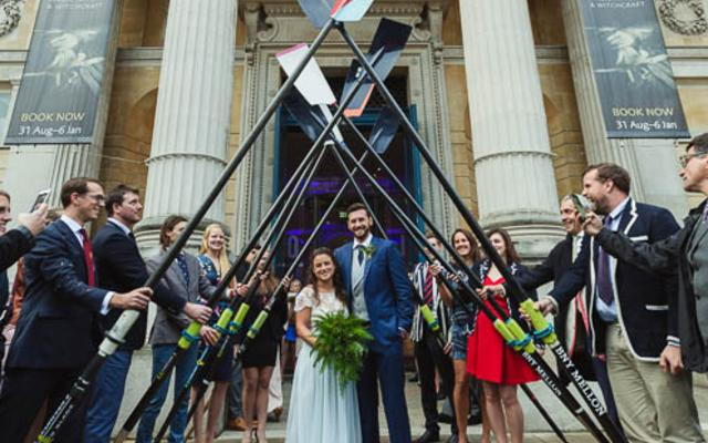 Alex Woods and Zoe de Toledo, on their wedding day, leaving the venue through an arch of rowing oars, lined by wedding guests