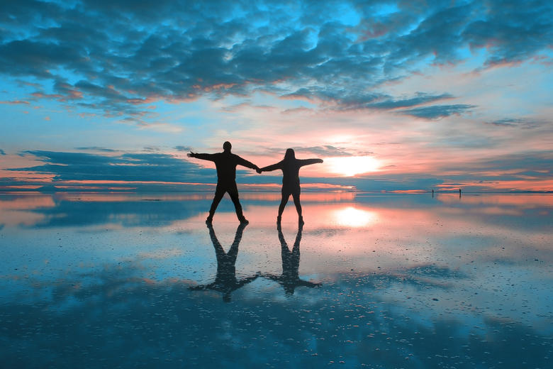 Two people holding hands on a wet beach, with the sun setting and visible below clouds