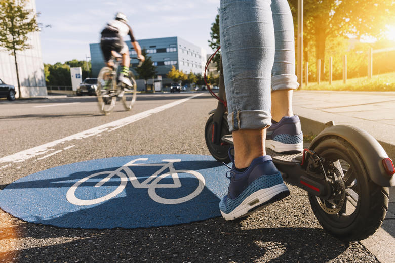 A close up view of an electric scooter as it ridden over a bicycle lane sign painted on a carraigeway