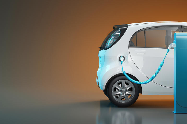 The back half of a white, electric car, which is plugged in and charging
