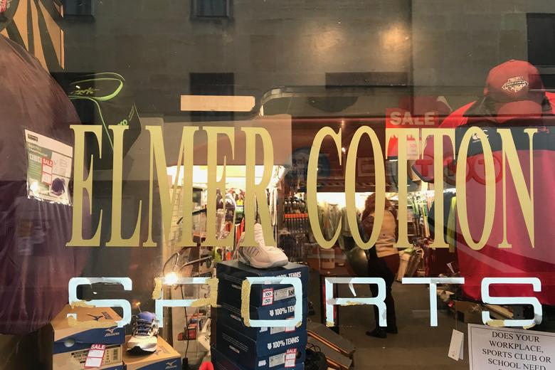 Looking through the window of Elmer Cotton Sports, with the name printed on the window