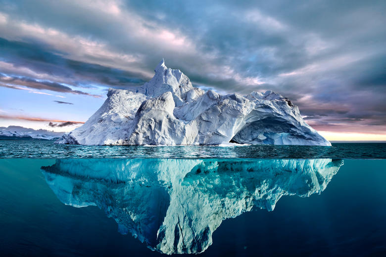 A large ice berg, with parts above and below the water level