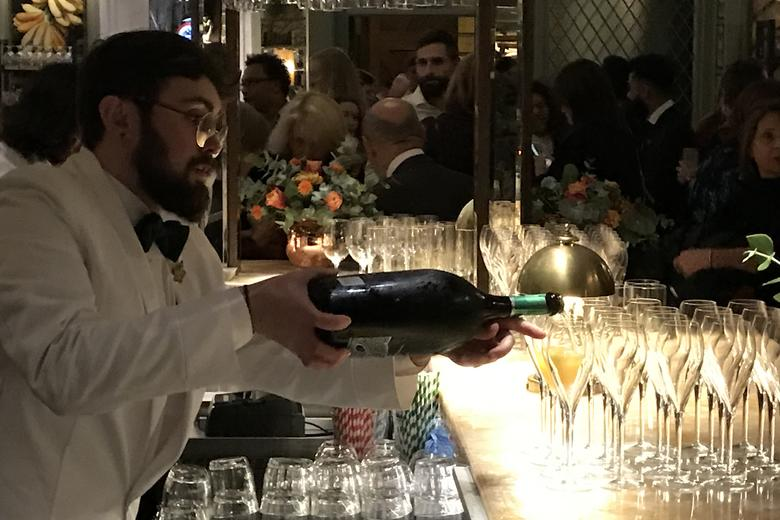 A barman, pouring glasses of wine