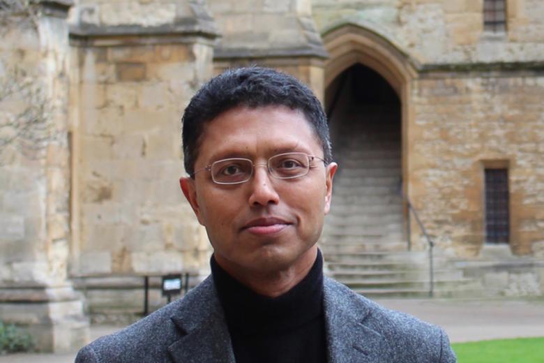 A head shot of Masud Husain, stood in an Oxford College quad