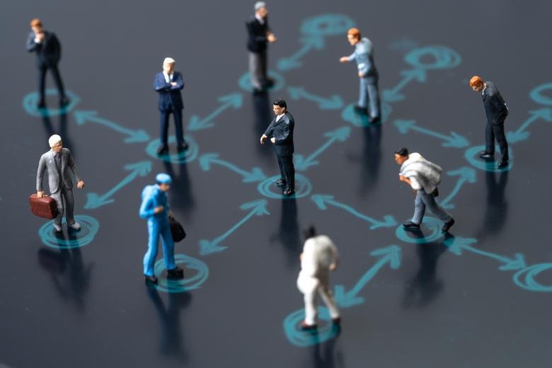 Toy figures of people, stood on a board, with lines drawn between them to indicate social distancing