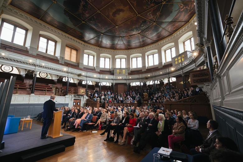 A view of the full auditorium, with Tom Steyer lecturing from a podium at the front