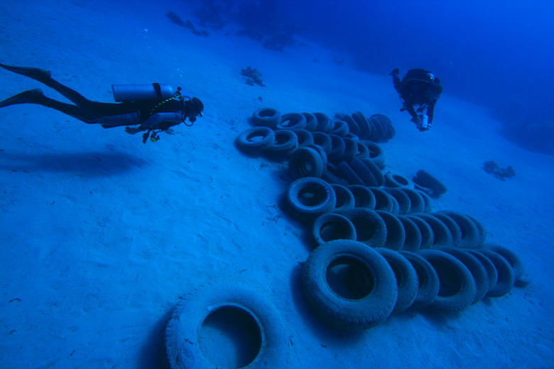 Two divers swimming down to a pile of car tyres on the sea bed
