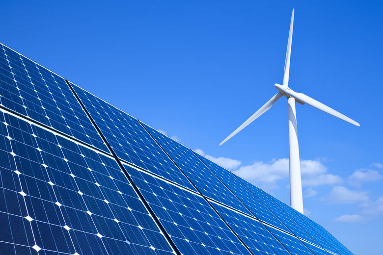 A wind turbine behind a solar panel