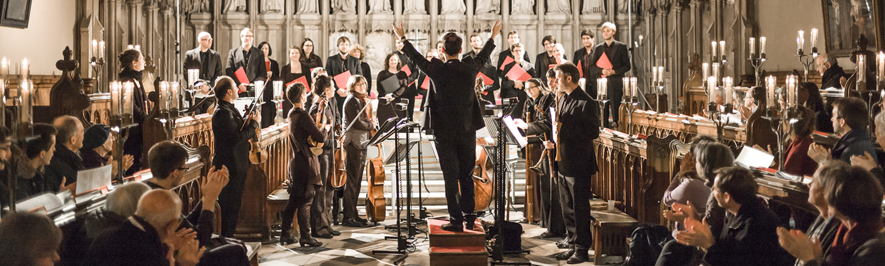 The Oxford Bach Soloists, in a church apse, are standing to receive applause from the audience in the nave in the foreground
