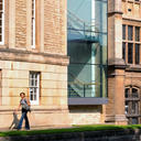 The exterior of the Radcliffe Science Library, with a woman walking in front of it