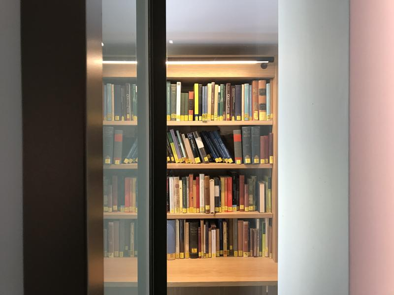 A view from an open glass door of books on a shelf
