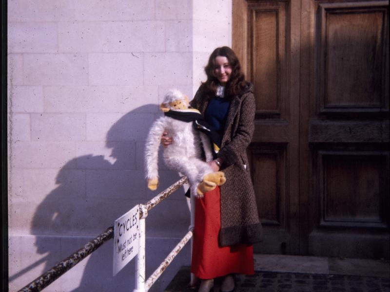 Nicky Bull (nee Harper) on college steps, holding a large white, cuddly monkey which is wearing a college scarf