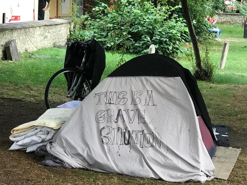 A tent in a graveyard - on the tent is written 'This is a grave situation'