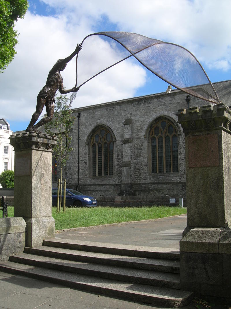 A sculpture of St. Andrew casting his net across two 3m. high pillars in front of the Minster Church in Plymouth.