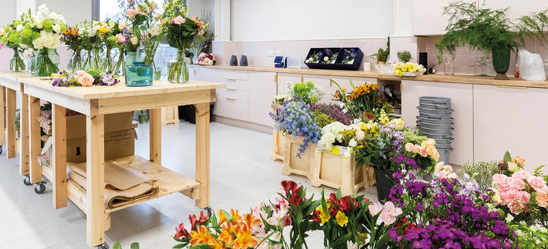 A room with table of bouquets of flowers, with equipment ready for dispatching them