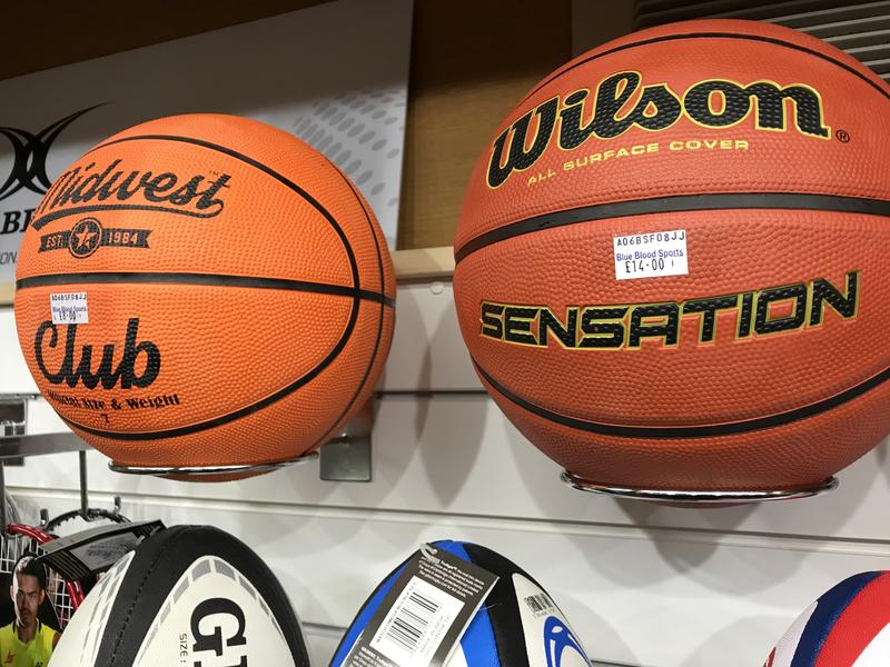 Two basketballs on a shelf in a sports shop, with the price stickers with the shop name 'Blue Blood'