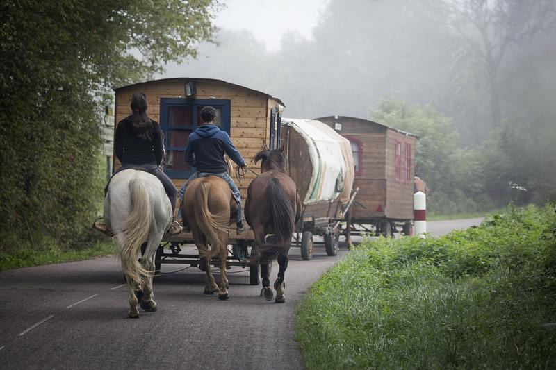 Three horses, two of which are being ridden, walking on a road behind three linked caravans, two of which are wooden and one is canvas