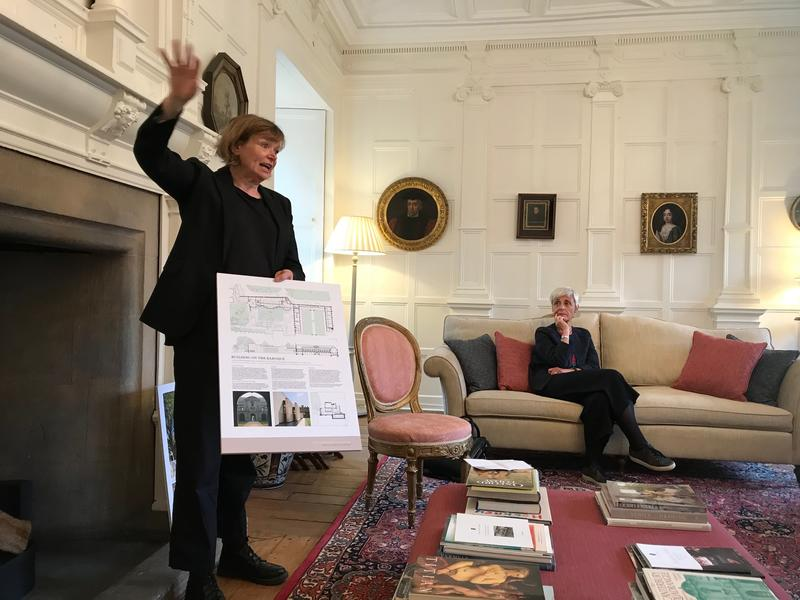 Claire Wright talking about St John's library whilst holding designs; the college President is seated next to her listening