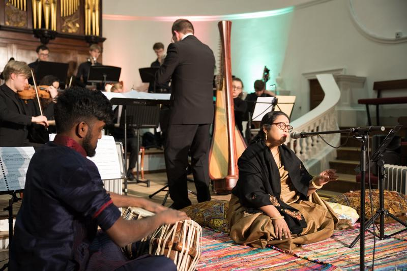 Shruti Jauhari, seated on the floor, singing and accompanied by a band