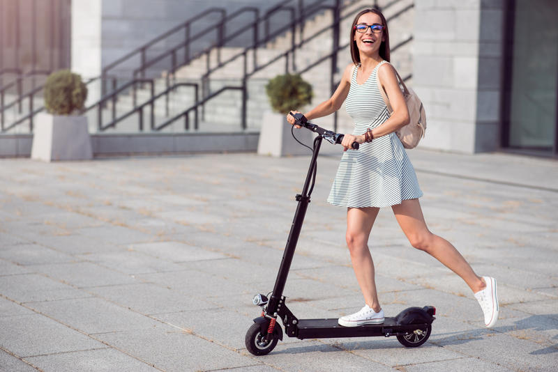 A smiling woman riding an electric scooter