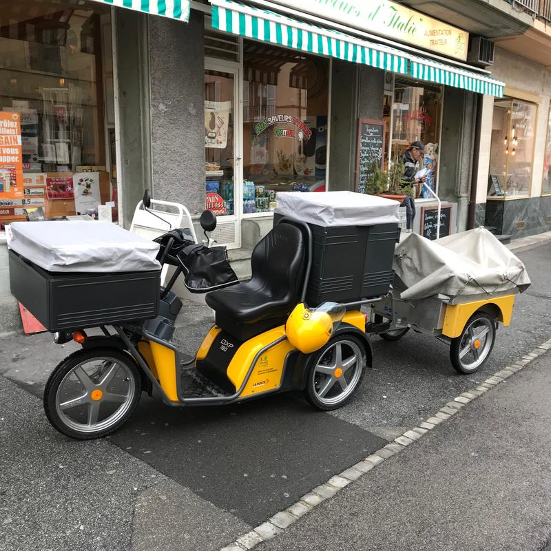 A Swiss Post electric vehicle parked outside a shop