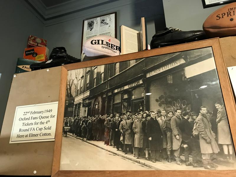 An old picture on display in the shop, which shows people queuing, with a note explaining the shop sold Oxford United FA Cup tickets in 1949