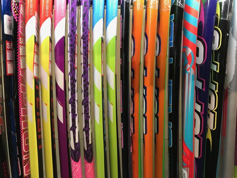A row of multi-coloured hockey sticks