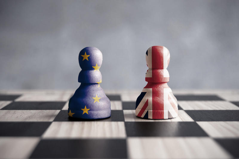 Two chess pieces on a board - one is painted in the colours of the EU flag, the other in the colours of the British flag