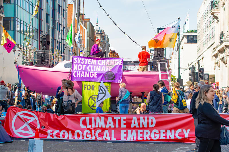 Particpants in the Extinction Rebellion demonstrations in London, holding banners on a pink boat, parked to block a street