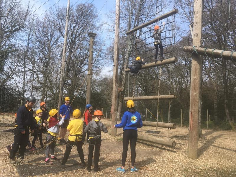Two chldren climbing up a cargo net on an assault course, while adults and other children watch from the ground