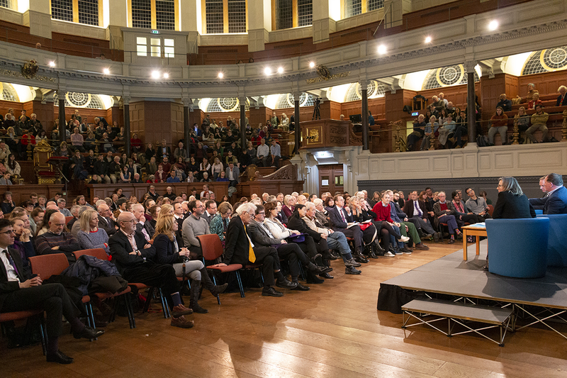 A view from behind the stage of the audience in the Sheldonian Theatre, with the stage and speakers just visible on the right of the picture