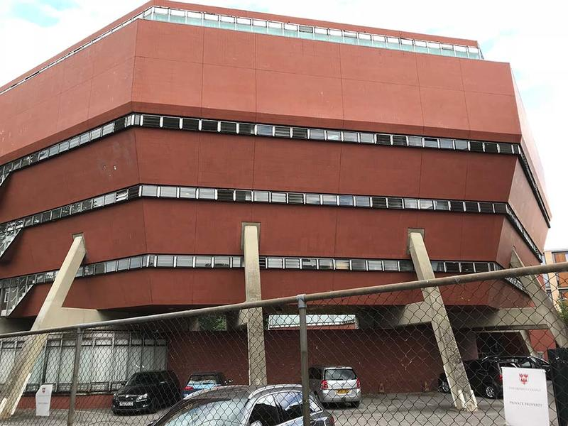 The Florey Building - an angular red building, tapering outwards, with car parking at the base
