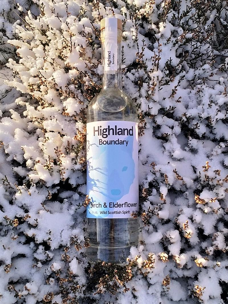 A bottle of Highland Boundary lying on snow covered heather