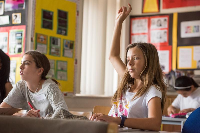 A young girl in a classroom, with her hand in the air