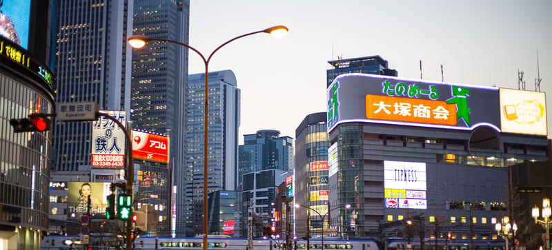 A Japanese street at dusk, lit by neon signs
