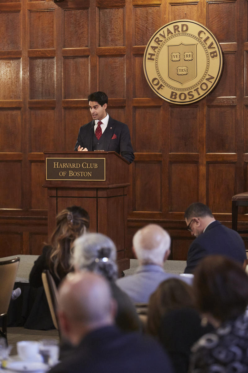 Jason Arora speaking behind a wooden lecturn with the Harvard Club of Boston seal behind him, and that wording on the lecturn