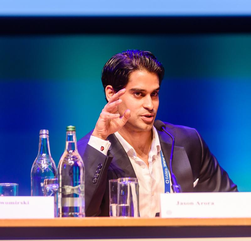 Jason Arora seated, speaking at a conference