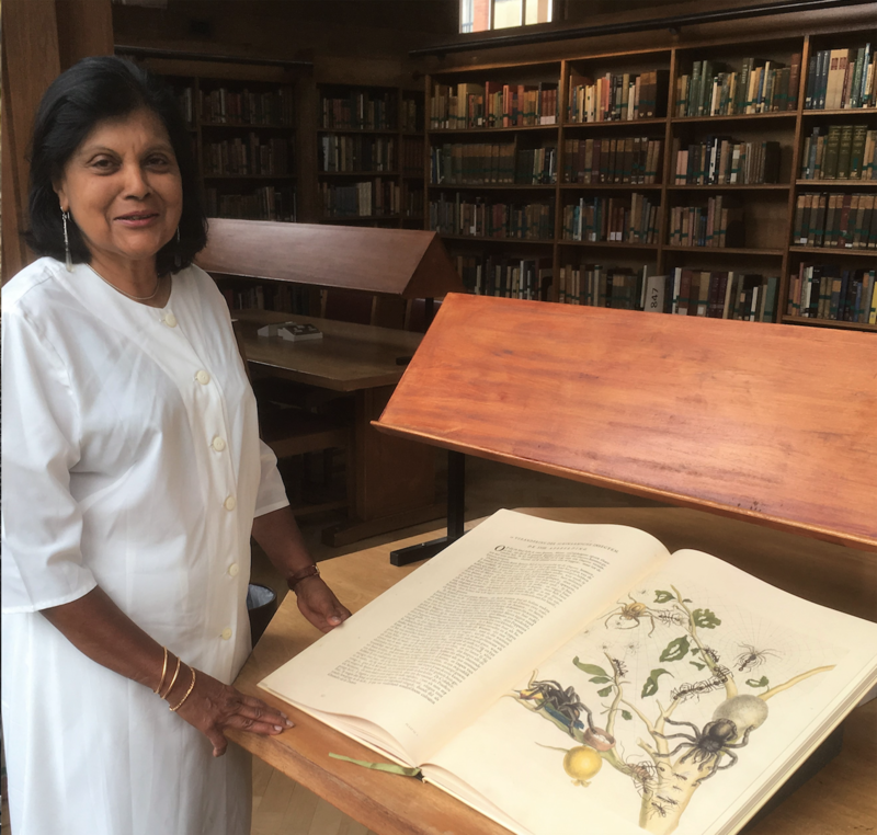 Jeyaraney Kathirithamby stood in a library next to a large open book, Merian's Metamorphosis Insectorum Surinamensium
