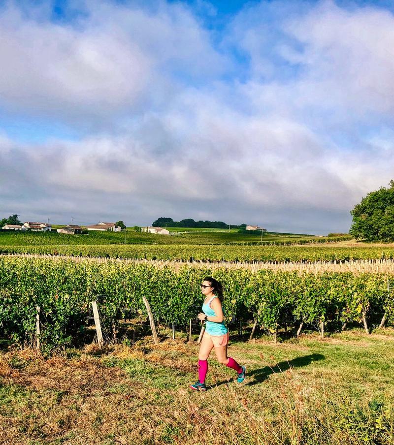 Katie Myint running passed a vineyard