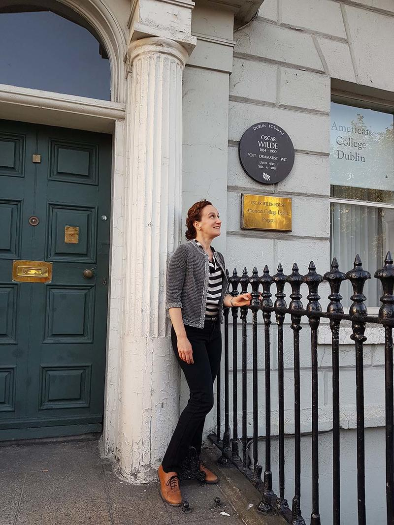 Michèle Mendelssohn stood outside a house which has a heritage plaque on it donoting it as Oscar Wilde's family home