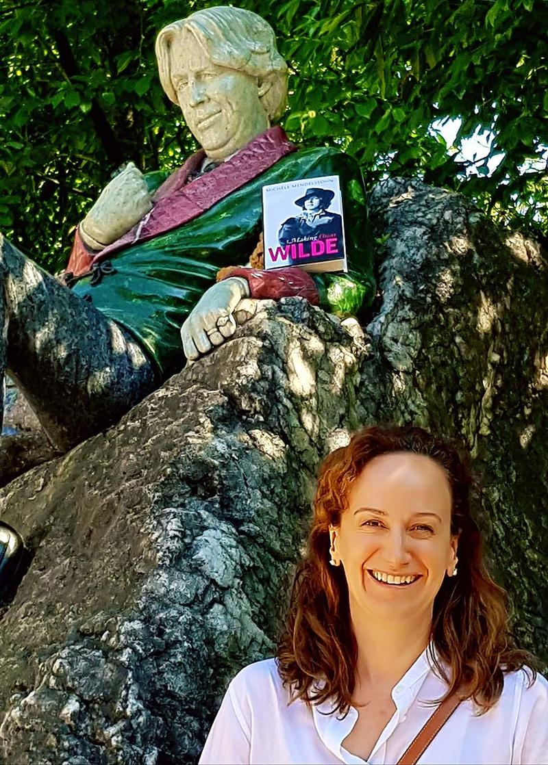 Michèle Mendelssohn at the Oscar Wilde Memorial Sculpture in Dublin - a copy of her book is resting in the statue's arm